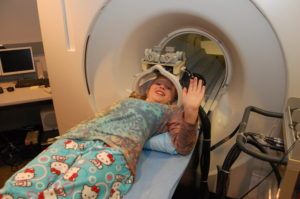 A child waves from the MRI simulator.