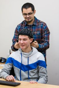 Lab staff adjusts EEG cap on participant